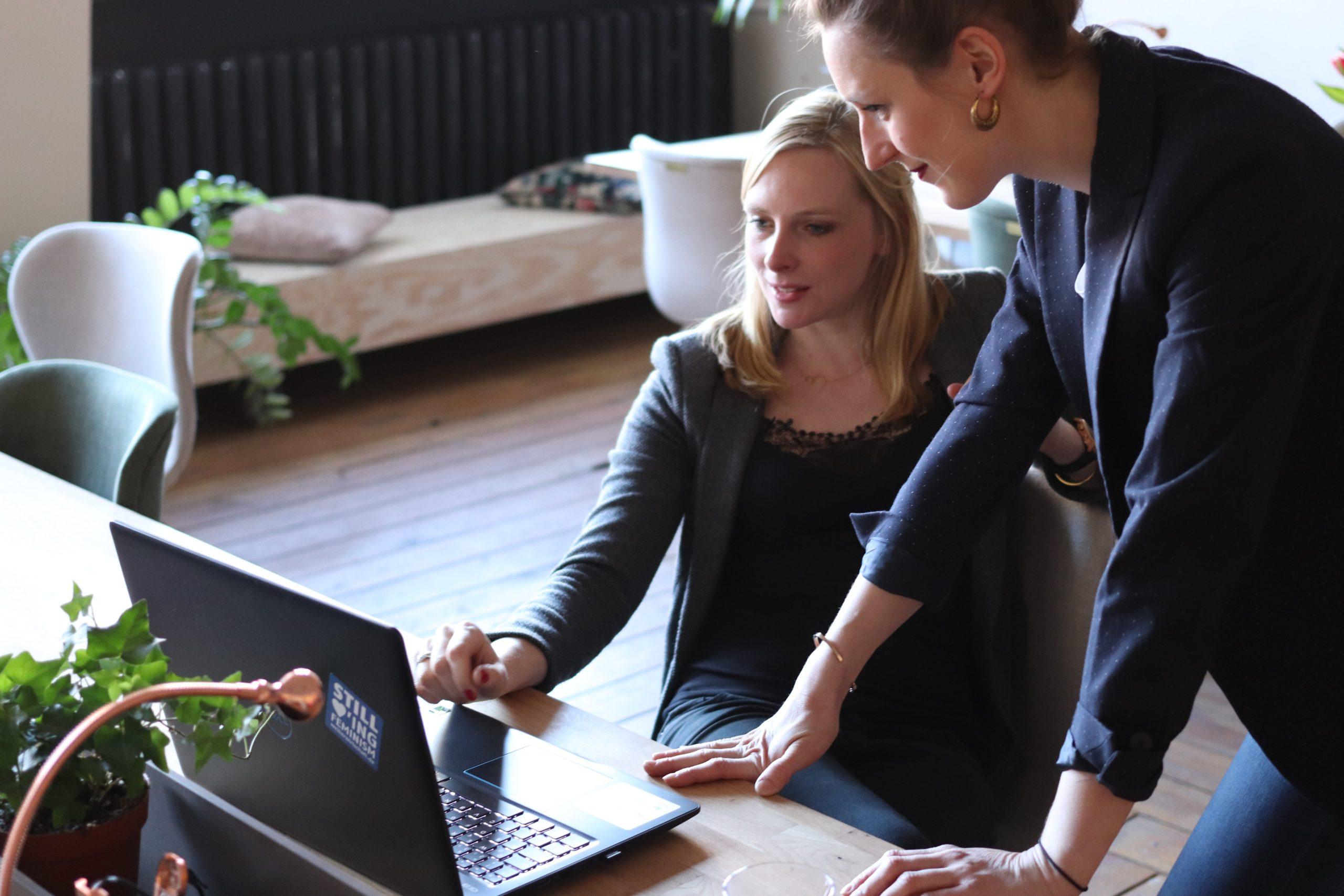 Duas mulheres olhando para uma tela e explicando algo.